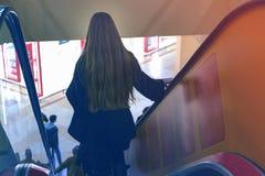 Muchacha abajo de la escalera móvil Fotografía de archivo