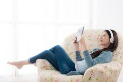 Muchacha abajo en la silla del sofá que disfruta de vacaciones del día de fiesta Fotografía de archivo libre de regalías