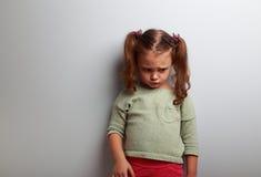 Muchacha abandonada infeliz del niño que mira abajo en fondo azul Fotografía de archivo