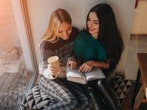 Muchacha absorbente en libro de lectura durante la rotura en café Libro de lectura precioso lindo de la mujer joven y café de con Imagenes de archivo