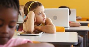 Muchacha aburrida que se sienta en el escritorio en sala de clase almacen de metraje de vídeo