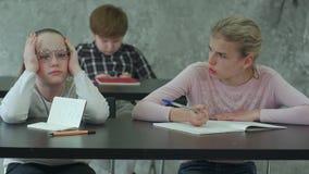 Muchacha aburrida que se sienta en el escritorio en la sala de clase de la escuela, discutiendo algo con el compañero de clase metrajes