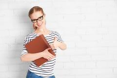 Muchacha acertada feliz del estudiante con el libro que muestra los pulgares para arriba Foto de archivo libre de regalías