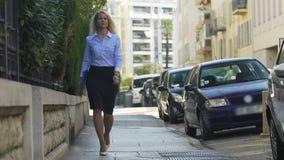 Muchacha acertada que camina con confianza a lo largo de la calle con la carpeta en sus manos almacen de video
