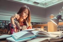 Muchacha acertada que estudia difícilmente en biblioteca Fotografía de archivo libre de regalías