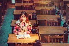 Muchacha acertada que estudia difícilmente en biblioteca Fotografía de archivo