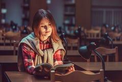 Muchacha acertada que estudia difícilmente en biblioteca Fotos de archivo