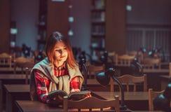 Muchacha acertada que estudia difícilmente en biblioteca Foto de archivo libre de regalías