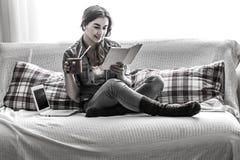 muchacha acogedora con un libro y una taza Imagen de archivo libre de regalías