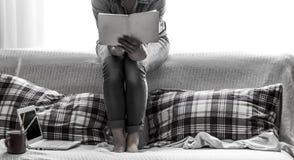 muchacha acogedora con un libro y una taza Imágenes de archivo libres de regalías
