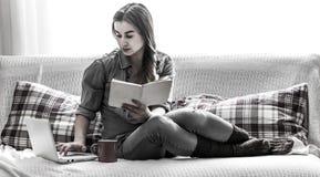 muchacha acogedora con un libro y una taza Fotos de archivo libres de regalías