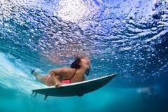 Muchacha activa en bikini en la acción de la zambullida en el tablero de resaca Foto de archivo libre de regalías