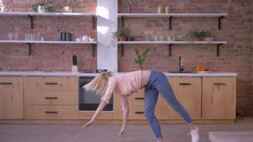 Muchacha activa feliz que hace tirón gimnástico en la cámara lenta en la cocina almacen de video