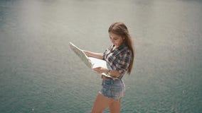 Muchacha activa joven del backpacker que comprueba con el mapa cerca de la superficie del agua del lago de la montaña en el día s almacen de metraje de vídeo