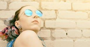 Muchacha activa joven del retrato del inconformista al aire libre en gafas de sol Foto de archivo