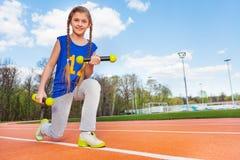 Muchacha activa que hace ejercicios con las pesas de gimnasia al aire libre Imágenes de archivo libres de regalías