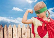 Muchacha adentro en el traje del super héroe que dobla sus brazos contra el cielo en fondo Imagen de archivo