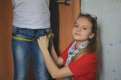 Muchacha adolescente 12 años de viejos juegos en la costura con la hermana - costurera Foto de archivo libre de regalías
