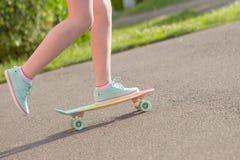 Muchacha adolescente abajo de la calle con un monopatín Fotos de archivo