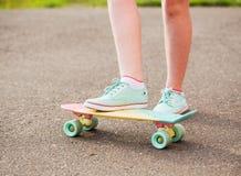 Muchacha adolescente abajo de la calle con un monopatín Imagen de archivo