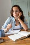 Muchacha adolescente aburrida del estudiante que estudia en casa Foto de archivo libre de regalías