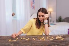 Muchacha adolescente aburrida que juega con la comida Fotos de archivo