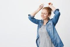 Muchacha adolescente adorable emotiva del jengibre que sonríe mientras que escucha la música vía los auriculares, celebrando smar Imagen de archivo libre de regalías