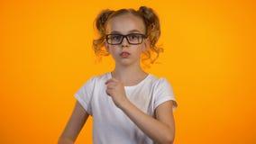 Muchacha adolescente adorable que ajusta las lentes y que cruza las manos en el pecho, pequeño empollón metrajes