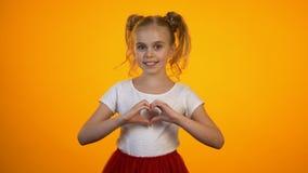 Muchacha adolescente adorable que hace el corazón con las manos, amor y cuidado, cardiología y salud almacen de metraje de vídeo