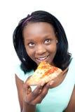 Muchacha adolescente africana sonriente que come una pizza Foto de archivo libre de regalías