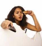 Muchacha adolescente afroamericana gorda joven con el telecontrol y la hamburguesa aislados, malsano obsesionado Fotografía de archivo