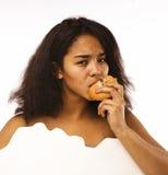 Muchacha adolescente afroamericana gorda joven con el telecontrol y la hamburguesa, malsano obsesionado Foto de archivo