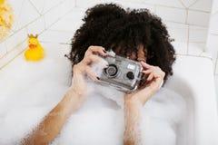 Muchacha adolescente afroamericana joven que pone en baño con la espuma, joyería del swag que lleva sin defectos, haciendo el sel Fotos de archivo libres de regalías