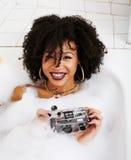 Muchacha adolescente afroamericana joven que pone en baño con la espuma, joyería del swag que lleva sin defectos, haciendo el sel Fotos de archivo