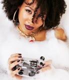 Muchacha adolescente afroamericana joven que pone en baño con la espuma, llevando Fotografía de archivo