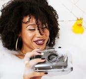 Muchacha adolescente afroamericana joven que pone en baño con la espuma, llevando Imagen de archivo