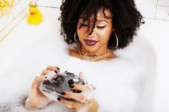Muchacha adolescente afroamericana joven que pone en baño con la espuma, llevando Imagenes de archivo