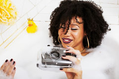 Muchacha adolescente afroamericana joven que pone en baño con la espuma, llevando Fotos de archivo