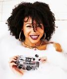 Muchacha adolescente afroamericana joven que pone en baño con la espuma, llevando Foto de archivo