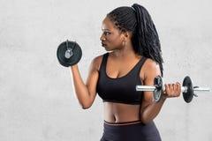 Muchacha adolescente afroamericana que se resuelve con pesas de gimnasia Fotos de archivo libres de regalías