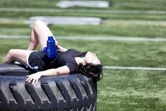 Muchacha adolescente agotada que descansa sobre el neumático del camión pesado en el centro del spo Fotos de archivo libres de regalías