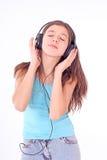 Muchacha adolescente agradable con los auriculares Foto de archivo