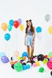 Muchacha adolescente agradable en el outfut fresco del verano que presenta con los globos Imagen de archivo libre de regalías