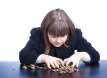 Muchacha adolescente agradable en un uniforme escolar que se sienta en una tabla y las cuentas Imagen de archivo libre de regalías