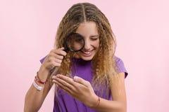 Muchacha adolescente alegre con el pelo rizado rubio largo que mira a través de una lupa Foto de archivo