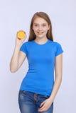 Muchacha adolescente alegre con la naranja Fotos de archivo