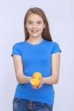 Muchacha adolescente alegre con la naranja Imagenes de archivo