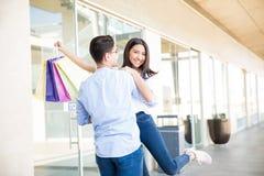 Muchacha adolescente alegre con los panieres que abraza al novio en el Mal Fotos de archivo libres de regalías