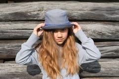 Muchacha adolescente alegre con los pelos largos en ropa casual y el sombrero azul que presentan por una pared de madera Forma de Fotos de archivo libres de regalías