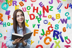 Muchacha adolescente alegre con un libro, letras Fotos de archivo